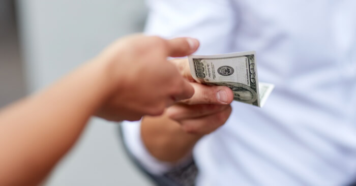 Close up of hands giving and receiving money